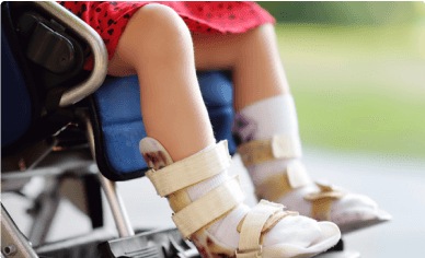 child sitting in wheel chair with leg braces